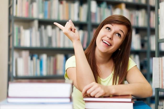 Mooie student die op copyspace richt