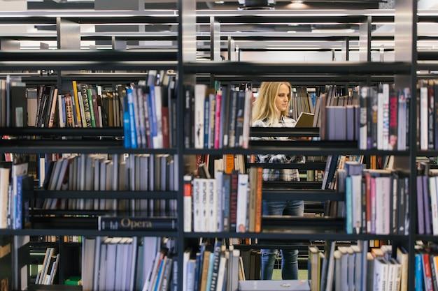 Mooie student in boekenplanken