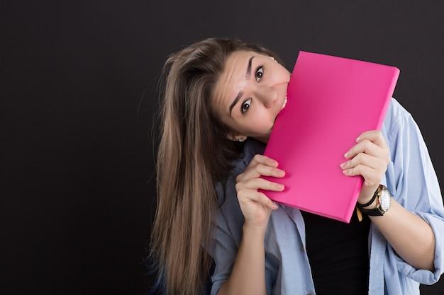 Mooie student in denim shirt met lang haar, op zwarte muur, knagen boek