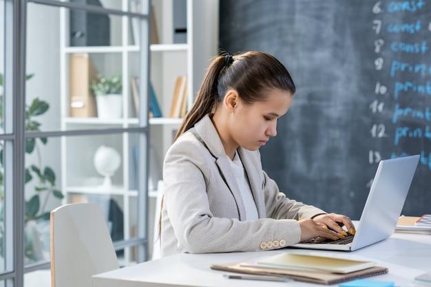 Mooie student in grijze jas zit door bureau voor laptop van schoolbord in de klas tijdens het invoeren van gegevens