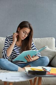Mooie student met donker haar gericht in leerboek, zit gekruiste benen op de bank