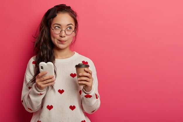 Mooie student met oosterse uitstraling geniet van vrije tijd met aromakoffie en moderne gadget, verbonden met draadloos internet