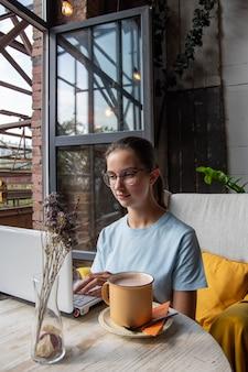Mooie studente die een laptop gebruikt, een bericht typt, op internet zoekt terwijl ze aan een tafel in een loftcafé zit, hard licht, verticaal frame. freelance-concept. ochtendontbijt in een café
