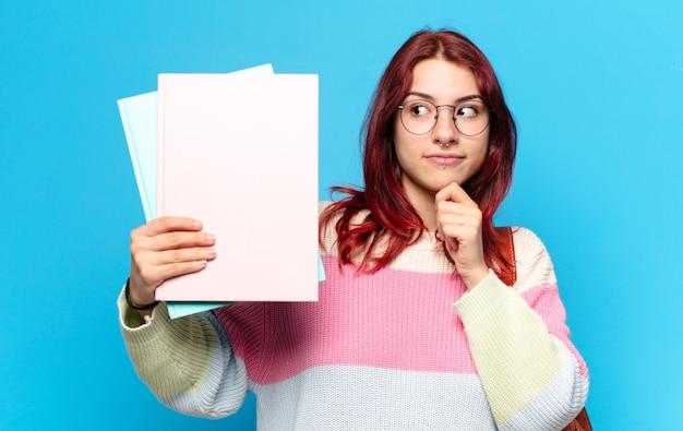 Mooie studentenvrouw die kleurrijke documenten houdt