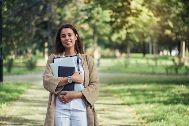 Mooie studentenvrouw staat met de map notebook en laptop op de universiteitscampus
