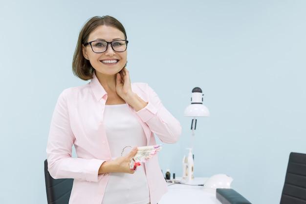Mooie succesvolle zelfverzekerde positieve zakenvrouweigenaar van schoonheidssalon, zorg voor handen en nagels, kopie ruimte