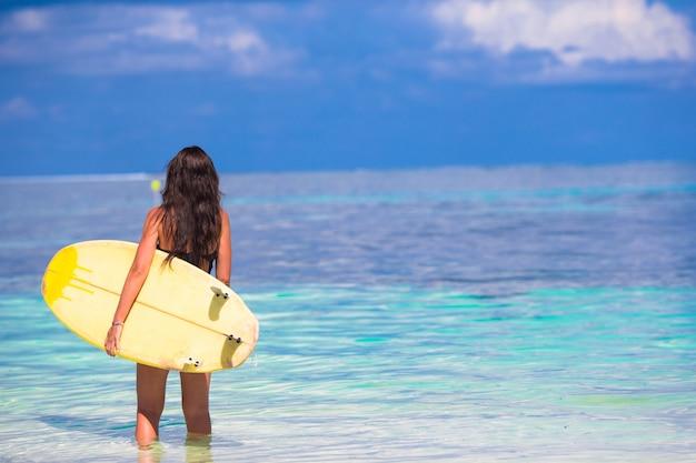 Mooie surfervrouw die tijdens de zomervakantie surfen