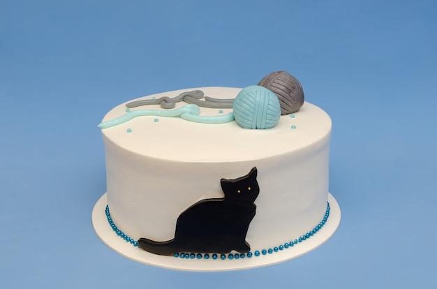 Mooie taart met decoratie van kat en bolletjes garen opgedragen aan het vierpotige huislid