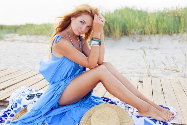 Mooie tan slanke roodharige vrouw met stijlvolle accessoires poseren op zonnige kust in de buurt van de oceaan. stro hoed, blauwe boho jurk.