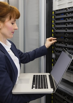 Mooie technicus die laptop met behulp van terwijl het werken aan servers
