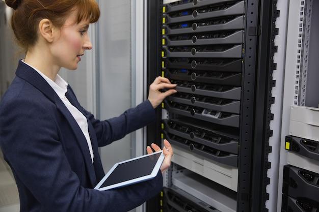 Mooie technicus die tabletpc met behulp van terwijl het werken aan servers