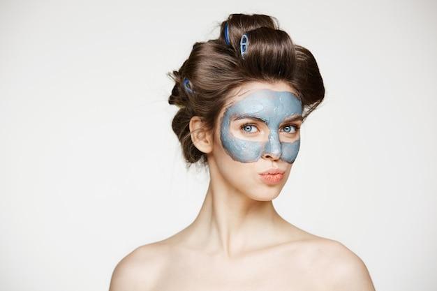 Mooie tedere naakte vrouw in haarkrulspelden en gezichtsmasker glimlachen. schoonheid gezondheid cosmetologie en huidverzorging.
