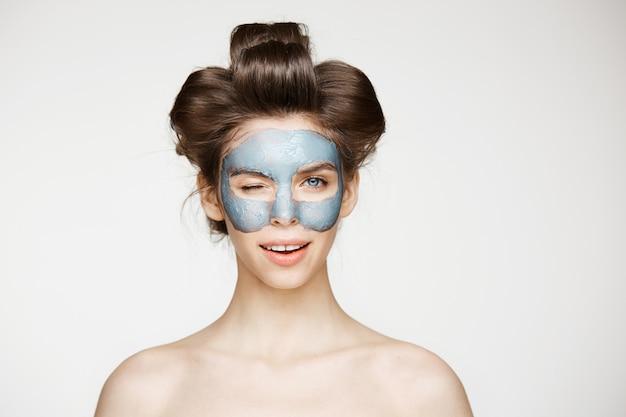 Mooie tedere naakte vrouw in haarkrulspelden en gezichtsmasker glimlachend knipogen. gezichtsbehandeling.