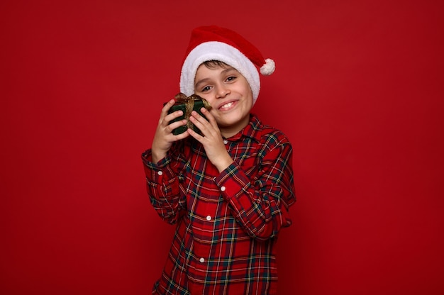 Mooie tedere schattige kleine jongen, schattig kind in kerstmuts en geruit hemd knuffelt zachtjes zijn kerstcadeau in groen inpakpapier met gouden strik, geïsoleerd op rode achtergrond met kopie ruimte