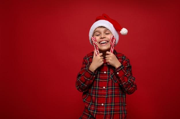 Mooie tedere schattige kleine jongen, schattig lachend kind in kerstmuts en geruit hemd knuffelt zachtjes kerstlolly's zoete gestreepte zuurstokken, geïsoleerd op rode achtergrond, kopieer ruimte voor advertentie