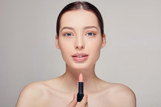 Mooie tedere vrouw met volle lippen met blote schouders met lippenstift in haar rechterhand kijkt recht in het frame door haar blauwe ogen