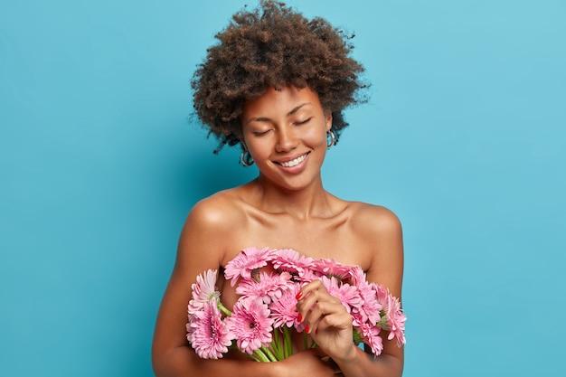Mooie tedere vrouw staat met gesloten ogen, naakt lichaam, draagt roze gerbera madeliefjebloemen, lacht vrolijk, heeft een gezonde donkere huid, geniet van een aangename geur,