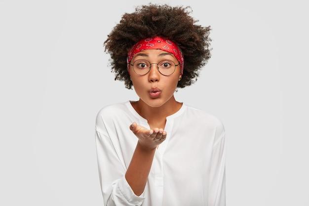 Mooie tedere zwarte vrouw met afro-kapsel, blaast airkiss, houdt de handpalm naar de mond, drukt liefde uit op afstand