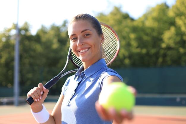 Mooie tennisser die de bal op de tennisbaan bedient.