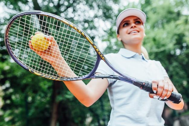 Mooie tennisspeler die bij camera op een zonnige dag met racket op haar handen glimlacht.