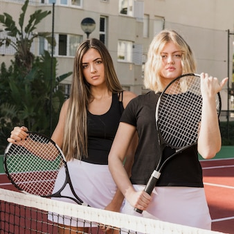 Mooie tennisspelers die rackets houden