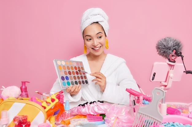 Mooie tevreden aziatische vrouw houdt oogschaduwpalet vast en gaat make-upgesprekken met volgers doen