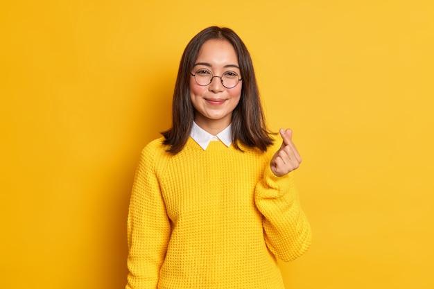 Mooie tevreden aziatische vrouw maakt koreaans als gebaar glimlacht zachtjes liefde betuigt aan iemand