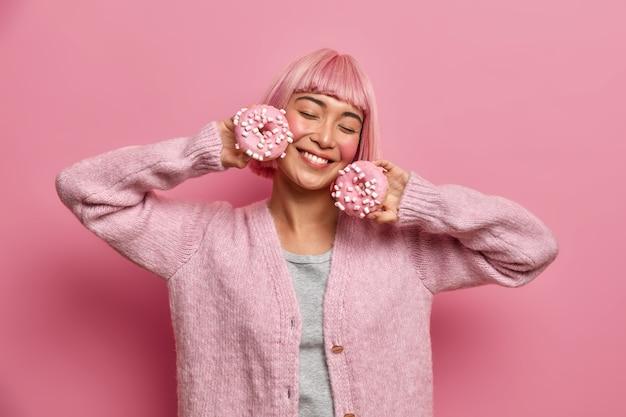 Mooie tevreden jonge vrouw glimlacht met gesloten ogen, houdt heerlijke geglazuurde donuts vast, stelt zich de aangename smaak van een zoet dessert voor, heeft roze haar geverfd, draagt een warme trui, heeft plezier, poseert binnen.