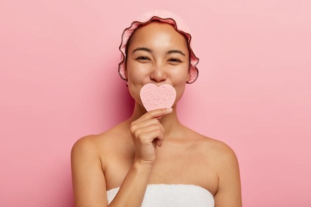 Mooie tevreden koreaanse vrouw houdt spons in vorm van hart, wast gezicht, reinigt huid, verzorgt haar teint, heeft beauty spa-behandeling, staat in badkamer gewikkeld in handdoek, draagt douchemuts