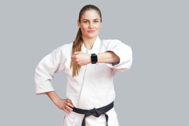 Mooie tevreden trotse jonge blonde atletische vrouw die zich voordeed en haar slimme horloge laat zien, glimlacht en naar de camera kijkt. vrouw met behulp van fitness armband. indoor studio-opname, geïsoleerd op een grijze achtergrond