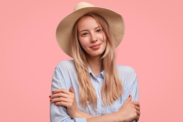 Mooie tevreden verlegen jonge vrouw model houdt de handen gekruist, kijkt positief naar de camera, draagt hoed en shirt