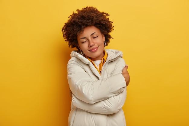 Mooie tevreden vrouw geniet van comfort in nieuwe winterjas, omhelst zichzelf, houdt de ogen dicht, voelt zich warm en tevreden, har krullend kapsel, geïsoleerd op gele achtergrond. mensen, kledingconcept