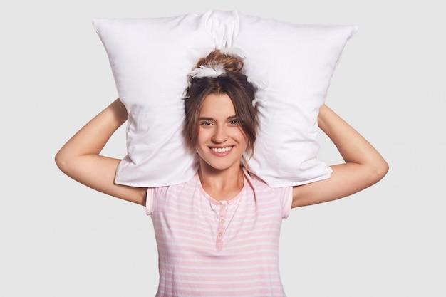Mooie tevreden vrouw met charmante glimlach, houdt hoofdkussen achter hoofd