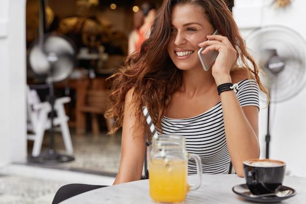 Mooie tevreden vrouw met schattige glimlach, geniet van recreatietijd in cafetaria, belt iemand via slimme telefoon
