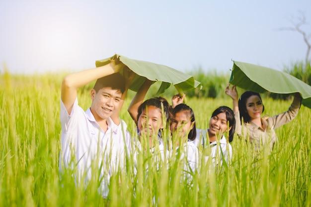 Mooie thaise leraar in eenvormige onderwijzende student om natuurlijke dingen bij openlucht te leren