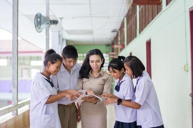 Mooie thaise leraar in eenvormige status bij de student van het klaslokaalonderwijs