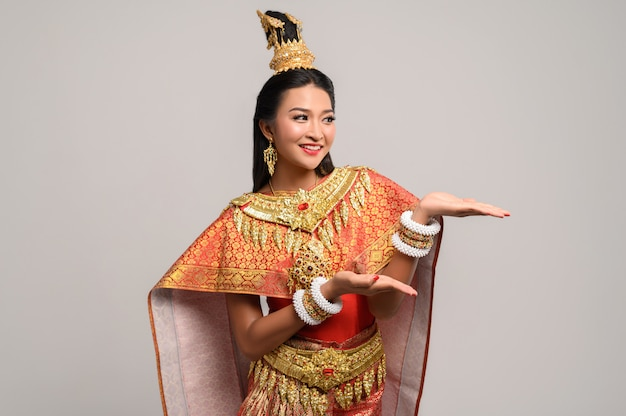 Mooie thaise vrouw die een thaise kleding en een gelukkige glimlach draagt.