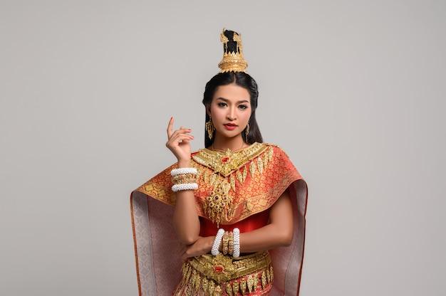 Mooie thaise vrouw die thaise kleding draagt en aan de kant kijkt