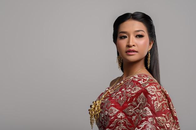 Mooie thaise vrouw die thaise kleding draagt en de bovenkant bekijkt
