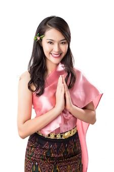 Mooie thaise vrouw die traditioneel thais kostuum draagt die welkome uitdrukking sawasdee doet, die op wit wordt geïsoleerd.