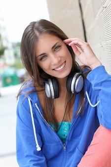 Mooie tiener buiten zitten met een koptelefoon