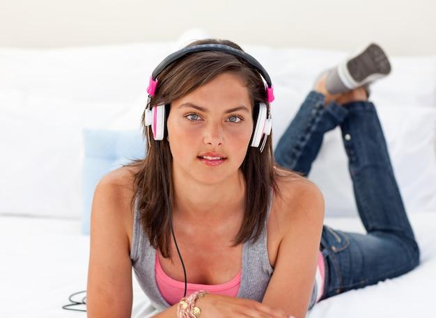 Mooie tiener die aan de muziek op zijn bed luistert