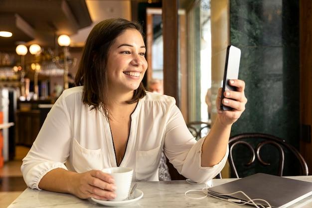 Mooie tiener die haar mobiele telefoon doorbladert