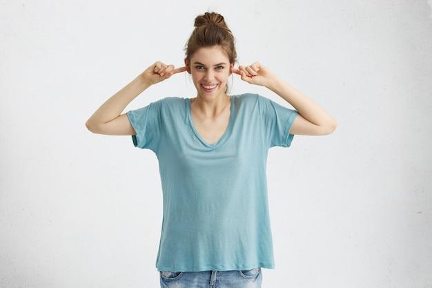 Mooie tiener die spijkerbroek en oversized blauw t-shirt draagt die oren met vingers dichtstopt en breed glimlacht, plagend, doet alsof ze niet luistert, iemand negeert.