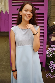 Mooie tiener in blauwe blouse, tegen violet houten venster met bloemen.