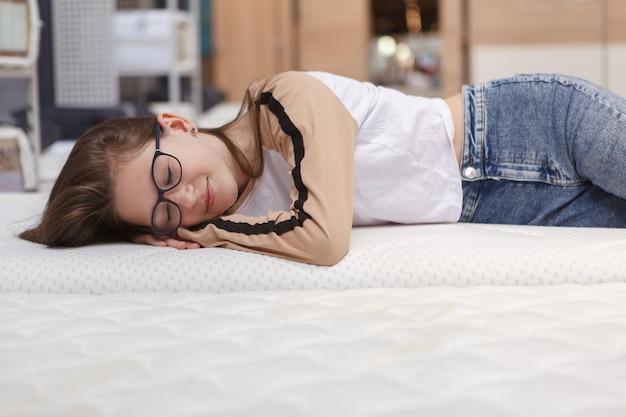 Mooie tiener meisje genieten van liggend op een nieuwe orthopedische matras bij meubelwinkel