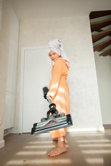 Mooie tiener meisje in een badjas doet huis schoonmaken met een stofzuiger