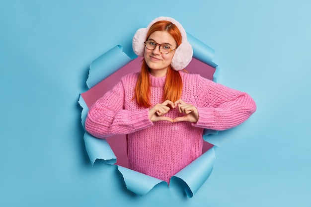 Mooie tiener meisje met natuurlijk gember haar draagt winter oorwarmers en gebreide trui vormen hart gebaar liefde uitdrukt.