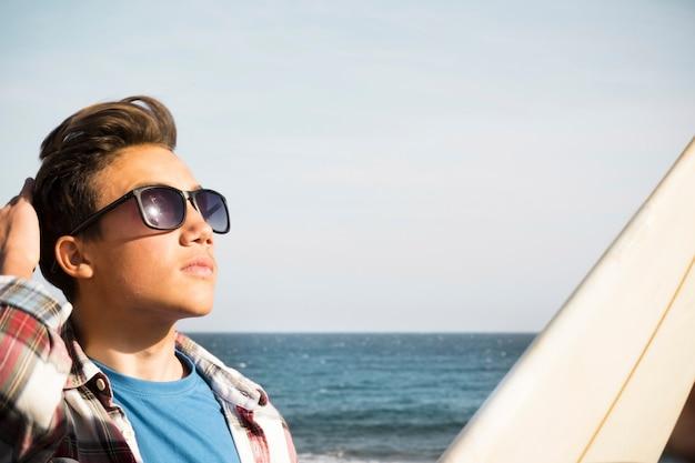Mooie tiener met zonnebril die naar de lucht kijkt - surferjongen met een surftafel op auto - vakantie- en reislevensstijl