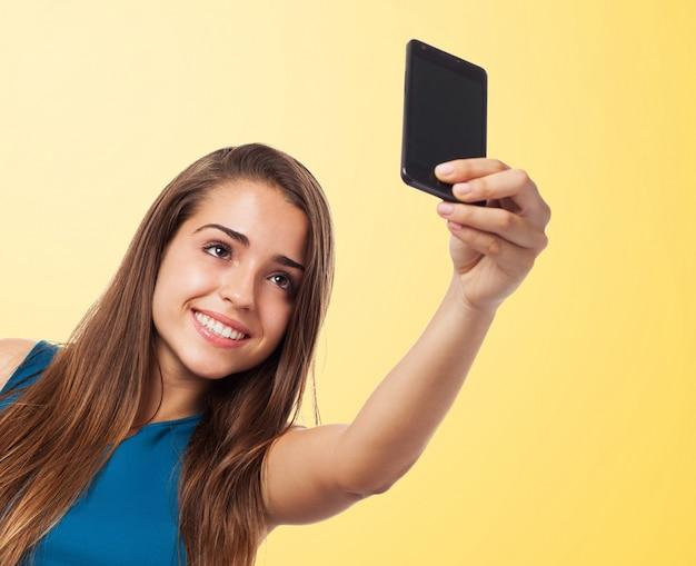 Mooie tiener nemen van een foto op een oranje achtergrond